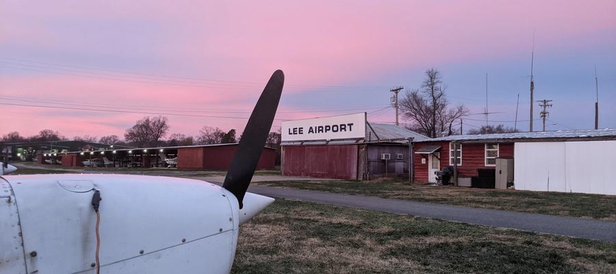 Airplane propeller against a pink and purple sky