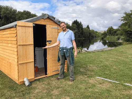 Man standing next to shed at the end of the canal