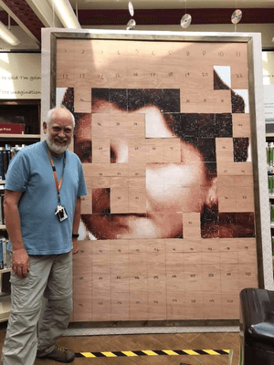 Man standing next to half completed image.