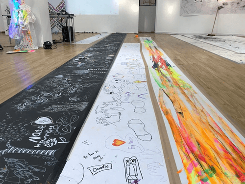 Three long sheets of painted paper on floor.