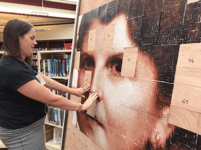 Librarian adding a finished card to the portrait.
