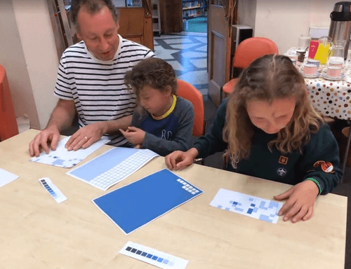 Man and two children at a table adding stickers to a sheet.
