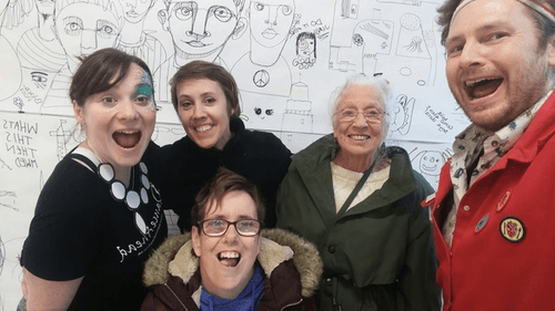Five people in front of a doodle wall.