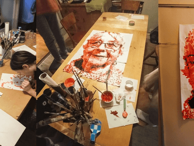 Three pictures in one. People painting, finished picture on table, finished picture on wall.