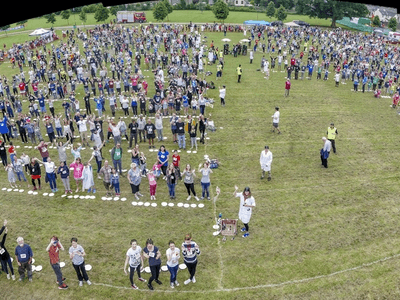 Bird's eye view of field with over 1000 people standing in lines next to pies
