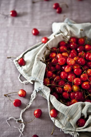 A fabric bag filled with red cherries