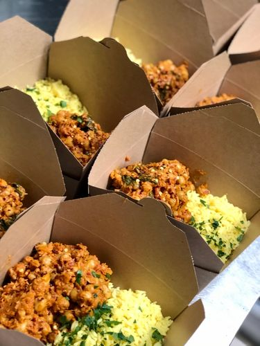 Shot of several takeaway boxes filled with a moroccan chickpea tagine and cauliflower rice.