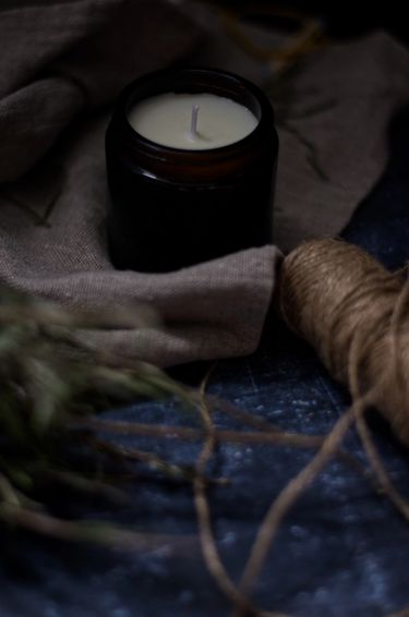 Candle on linen surrounded by natural thread