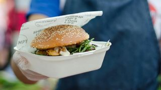 Close up of a hand presenting a burger in a burger box with Shrimpy's food wrap — a London food stall