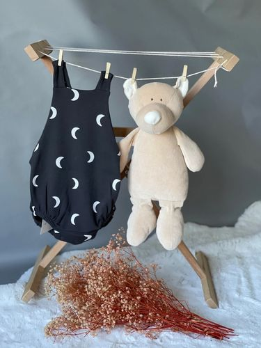 Picture of a baby onesie with a moon print in navy hanging beside a soft toy