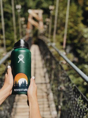 Hands holding a stainless steel bottle on a bridge in the forest