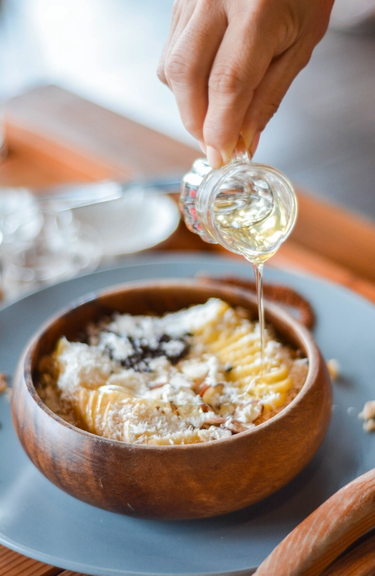 Porridge topped with fruit, nuts and coconut shavings in a wooden bowl with a hand drizzling honey from a little glass