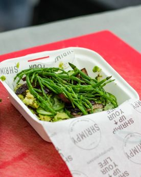Picture of a burger topped with samphire from a London based food stall specialising in shrimp burgers, preparing a shrimp burger at their food stall in Broadway Market