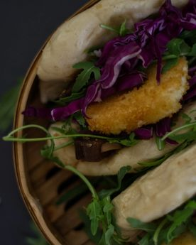 Close up shot of bao buns (gua bao) with rocket, cabbage, and fried goats cheese in a bamboo steamer
