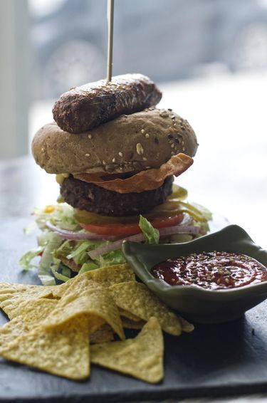 Head shot of a towering burger with Beyond Meat (Vegan) Sausage, Patty, vegan bacon, salad and a side of nachos with tomato sauce