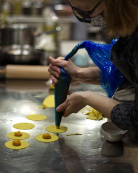Woman piping a pumpkin filling into fresh ravioli in an industrial kitchen