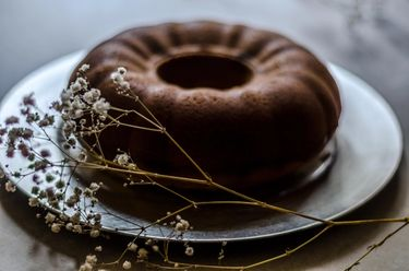 Cooked unsliced bundt cake on a silver cake plate, with dried flowers as decoration