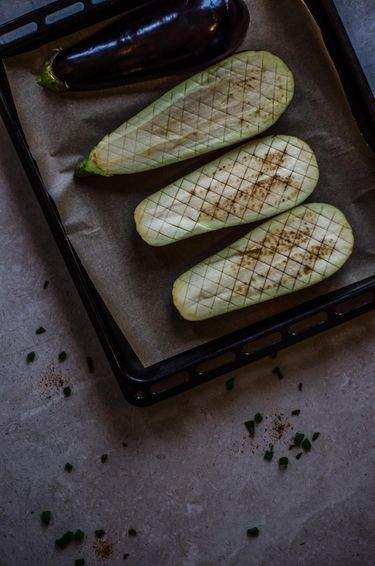 Four halves of raw aubergine on a baking tray