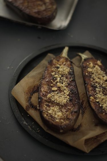 Close up of two halves of a roasted aubergine on a round metal tray