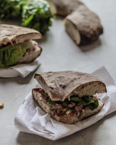 Several slices of Maltese ftira bread or hobz biz-zejt — a sandwich stuffed with tuna, capers, olives, goats cheese, lettuce, pickled vegetables and more.