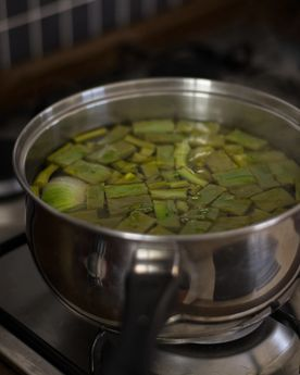 Full shot of a pot with sliced cactus pads (cactus leaves / cactus paddles / nopales) on a stove