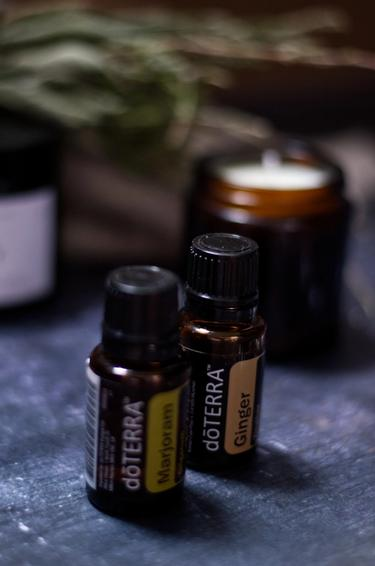 Two bottles of essential oils standing in front of a candle