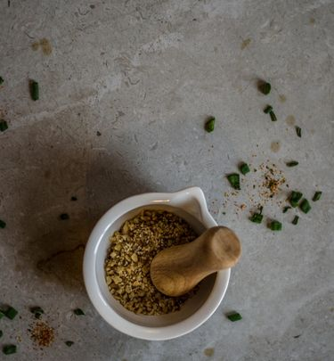 Bowl with dukkah (crushed nuts and seeds) on a surface sprinkled with chopped scallions