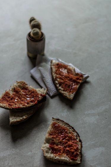 Three slices of Maltese bread with a tomato paste spread