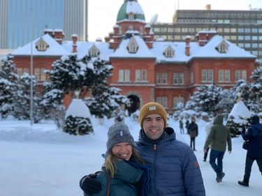A couple posing opposite the town hall of Sapporo, Japan