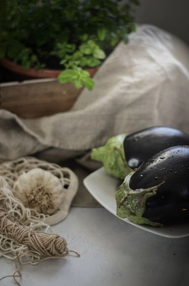 Two aubergines in a plate surrounded by items on a table