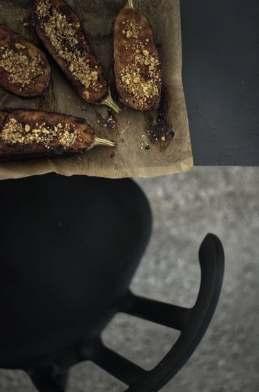 Top view of a tray of roasted aubergines and a chair