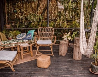 Outdoor are of restaurant The Nesting Table at glamping boutique hotel The Birdhouse El Nido showing a hammock, wooden tables and chairs surrounded by lush plants