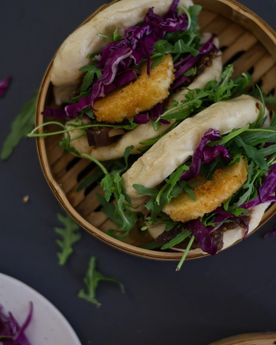 Bao buns (gua bao) with rocket, cabbage, and fried goats cheese in a bamboo steamer