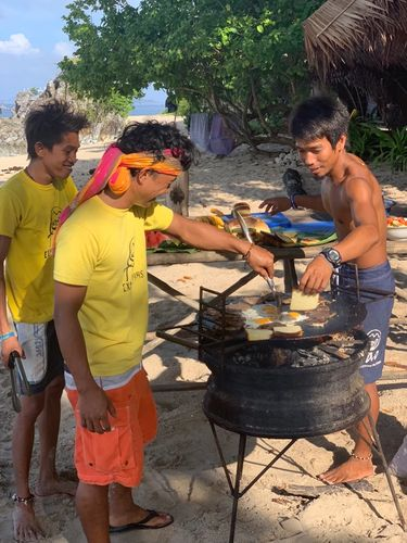 Men cooking food on a bbq on the beach
