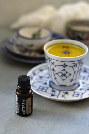 Turmeric milk in a bone china tea cup and saucer with a bottle of ginger essential oil next to it