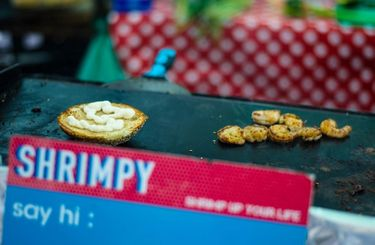 Grill with a burger bun besides a handful prawns and the logo of food stall, Shrimpy in London