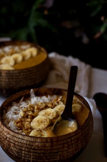 Close up shot of two smoothies in coconut bowls besides and indoor plant