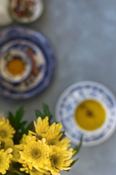 Overhead shot of turmeric milk in a bone china tea cup and saucer