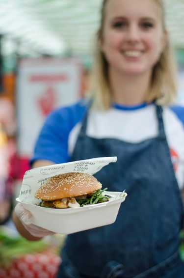 Picture of founder of Shrimpy, a London based food stall specialising in shrimp burgers, handing out a shrimp burger at their food stall in Broadway Market