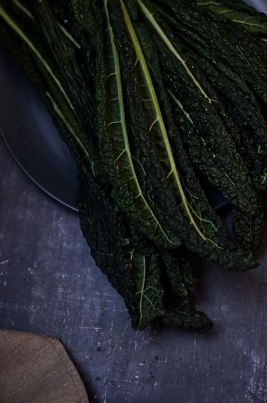 Kale leaves on a plate on a blue background