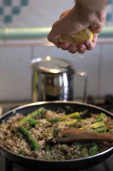 Pan with buckwheat and asparagus being cooked on a stove