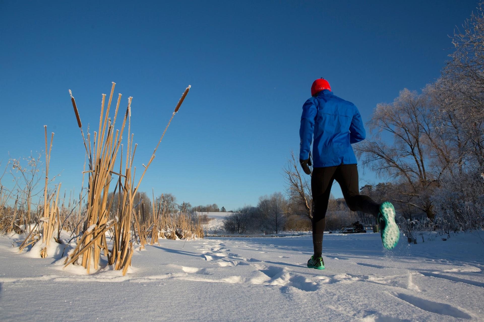 Mann løper om vinteren på snø