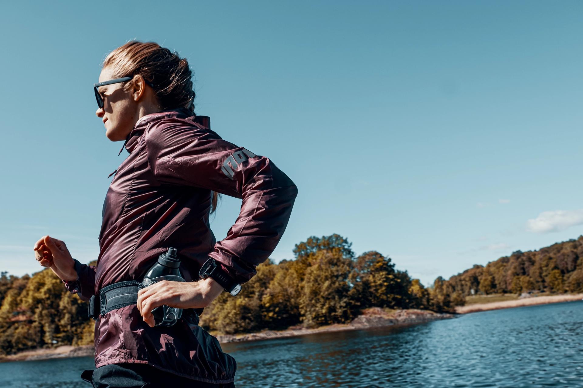Dame løper med solbriller ved vann