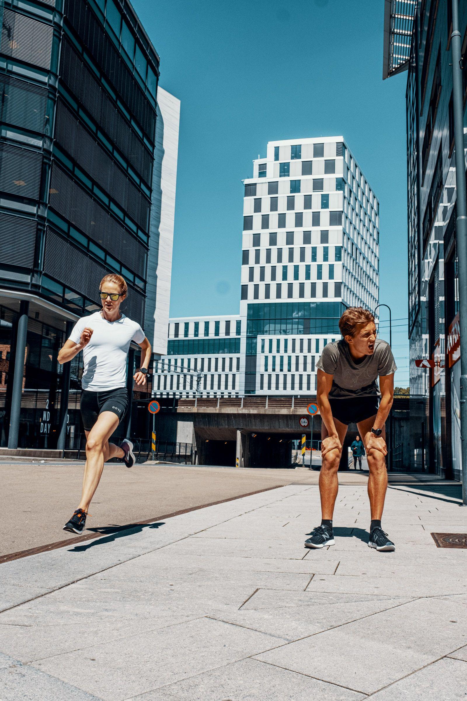 Ung dame og mann løper i byen