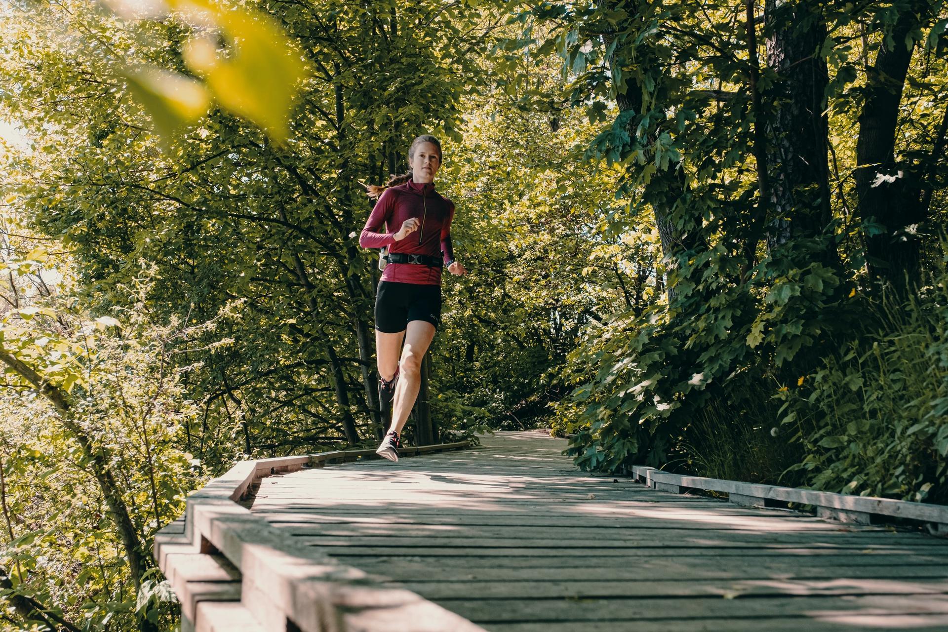 Dame løper på gangvei i park