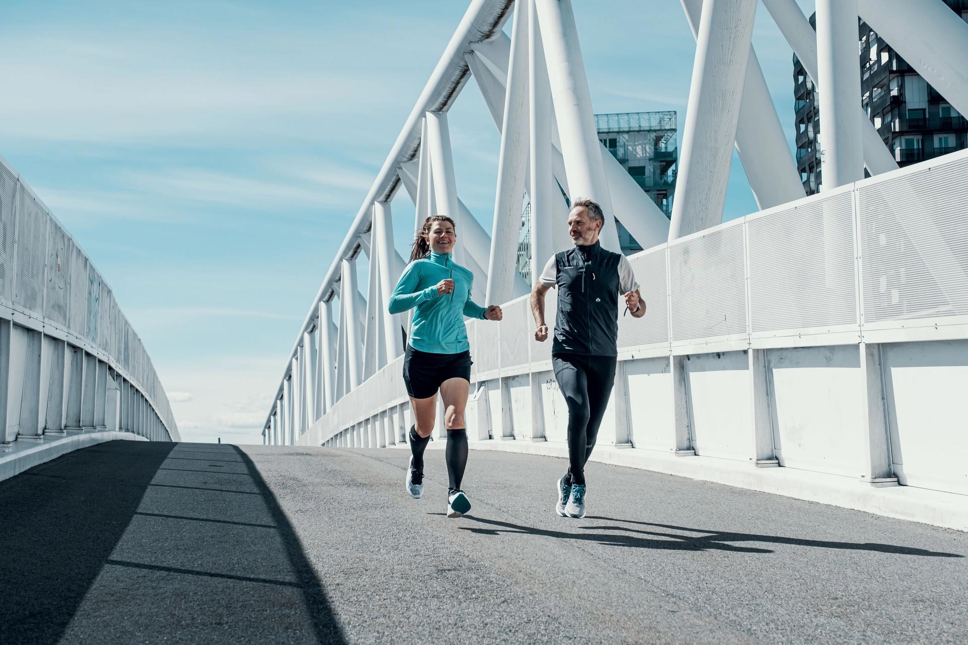 mann og dame løper over bro