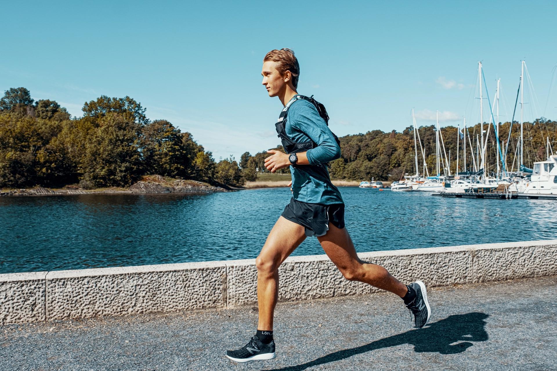 Mann løper langs sjøen med løpevest