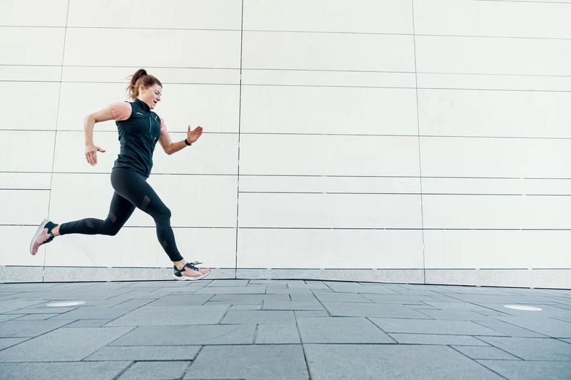 Dame løper langs bygning