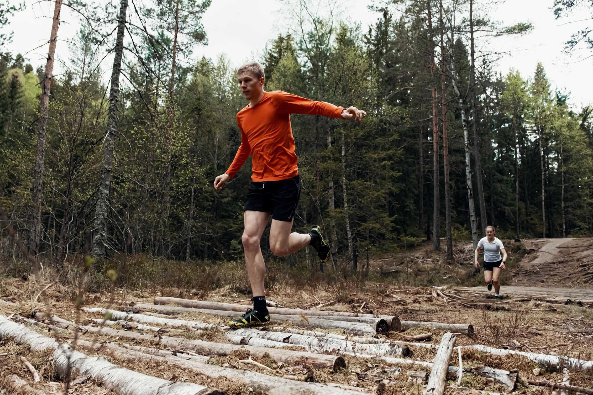 Ung mann løper i terrenget over stokker