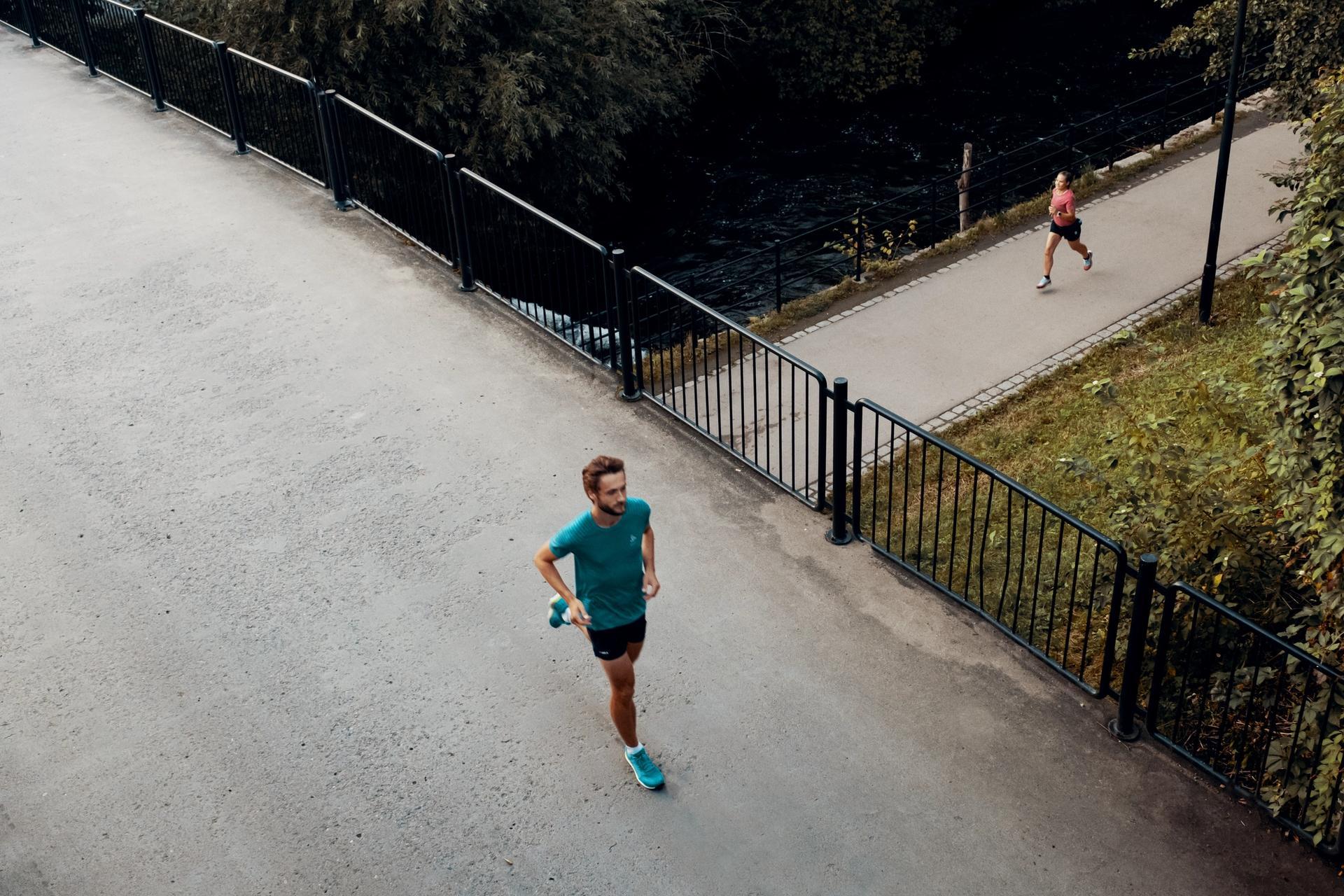 To løpere kryssende på asfalt